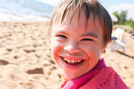 Beautiful Boy With Downs Syndrome Sitting at the Beach