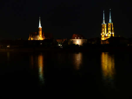 Ostrow Tumski at night. Illuminated town house and collegiate church. Gothic cathedral of St. John the Baptist on Tumski island. Wroclaw and one of the famous landmarks in the city. Reflection in the Odra River. poland