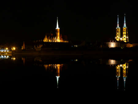 Ostrow Tumski at night. Illuminated town house and collegiate church. Gothic cathedral on Tumski island. Wroclaw and one of the famous landmarks in the city. Reflection in the Odra River. poland