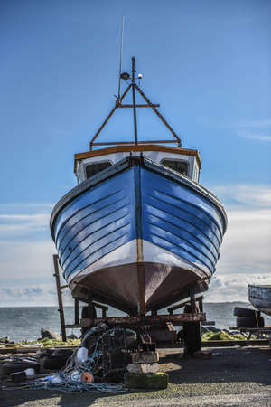 lobster boat: Blue wooden fishing boat sat over lobster pots in a boat yard