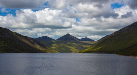 expansive: Wide expansive landscape showing a flat calm blue lake surrounded by a mountain range