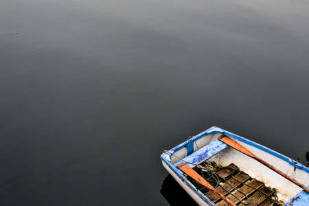 フラットな静かな湖の青の手漕ぎボート