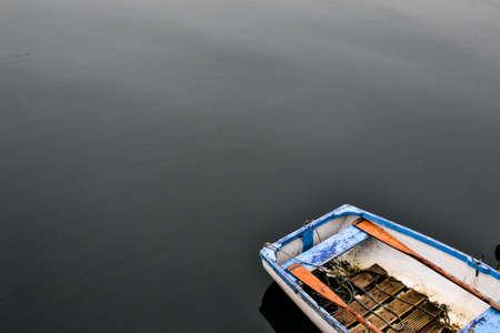 Blauw roeiboot op een vlakke kalme meer Stockfoto - 54270699