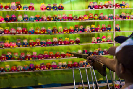 Carnival game shooting pop-caps at stuffed dolls for prize at festival in Thailand