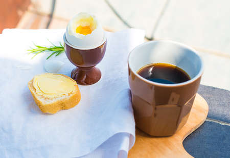 Outdoor breakfast with boiled egg and cup of coffee photo