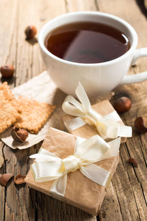 Cup of tea with gift boxes on old wooden background Stock Photo