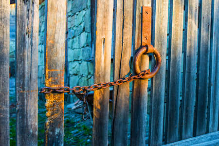 Old wooden gate with rusty chain photo