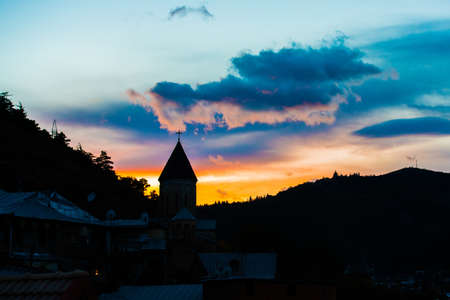 Silhouette of church and mountain in sunset photo