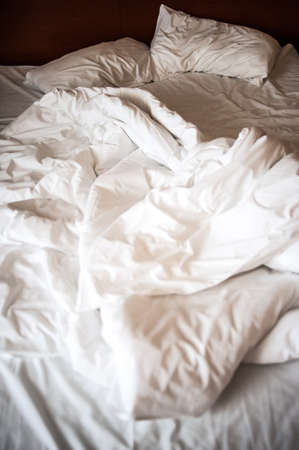 Unmade bed with white linens in the morning Stock Photo