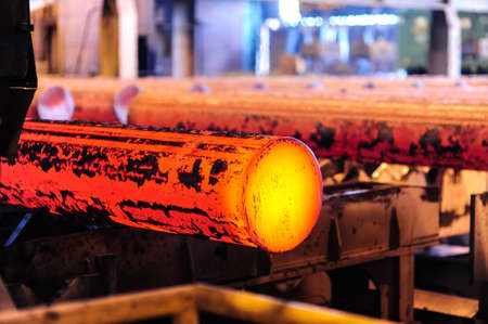 Hot steel blanks coming out of furnace Stock Photo
