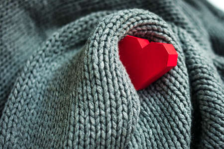 Paper heart in knitted grey scarf
