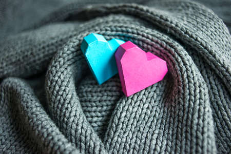 Paper hearts in knitted grey scarf