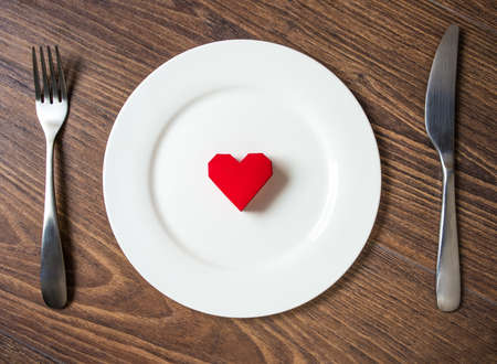 Red heart on a plate, fork and knife on wooden background