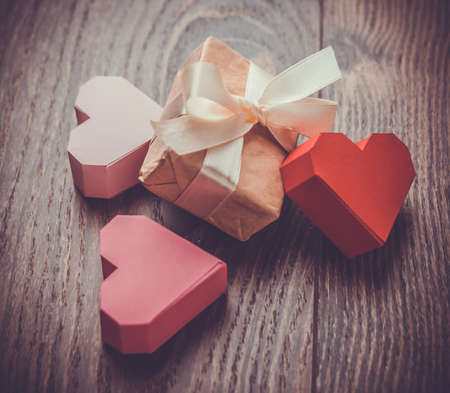 Bright paper hearts and gift box on wooden background