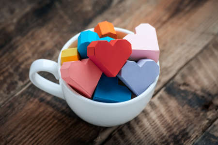 Bright paper hearts in white mug on wooden background