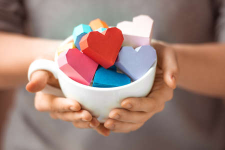 Bright paper hearts in mug in woman hands
