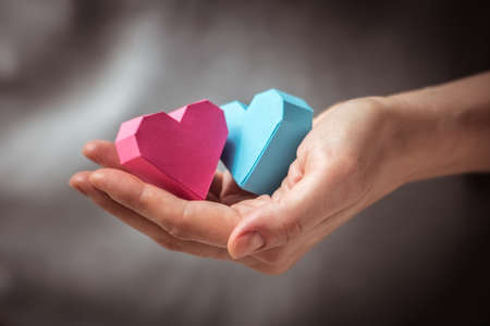 Bright paper hearts in woman hands