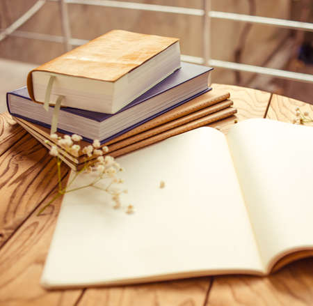 Books, flowers and opened diary on wooden table Imagens