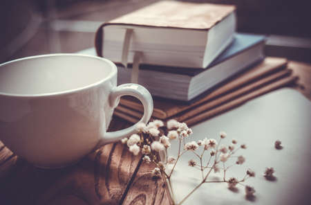 Books, flowers, white cup and opened diary on wooden table