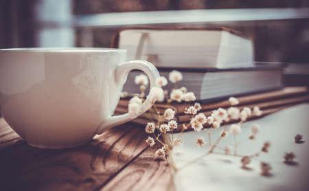 Boeken, bloemen en witte kop op houten tafel Stockfoto