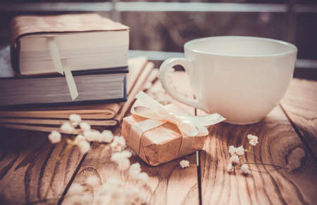 Books, flowers, white cup and wrapped gift box on wooden table