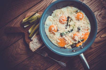 scrambled eggs: Huevos revueltos con puerro en el molde sobre la mesa de madera