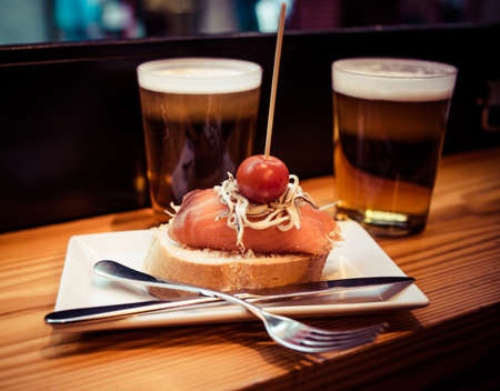 spanish tapas: Pinchos or pintxos, traditional Basque Country appetizer. Served with beer