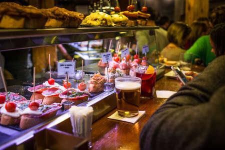 MADRID, SPANJE - 12 maart: Mensen eten in de typische tapas en pinxos bar in de wijk La Latina 12 maart 2014 in Madrid, Spanje. La Latina is bekend om zijn tapas bars en fantastische restaurants.