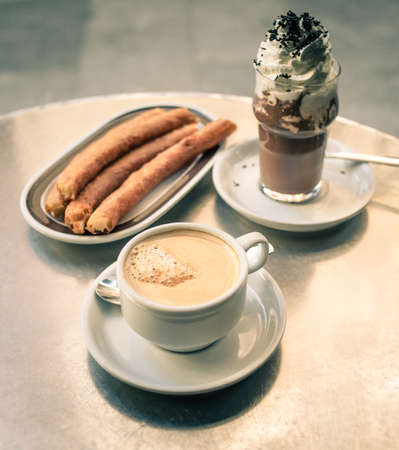 Coffee, churros and iced chocolate in spanish cafe. Toned in vintage colors photo