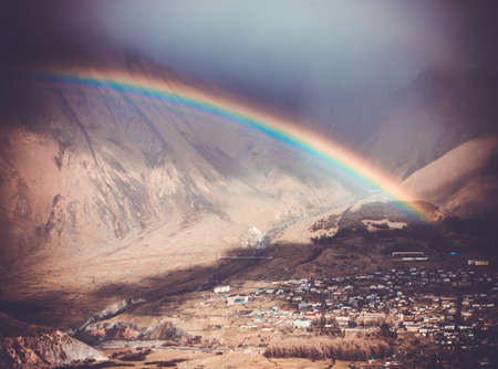 Bright rainbow after rain in Caucasus mountains near Kazbek (Kazbegi), Georgia. Picture toned in retro style photo