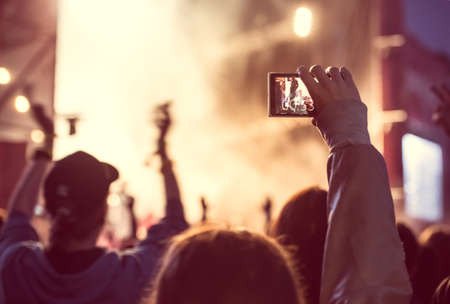 Close up of recording video with smartphone during a concert. Toned picture Фото со стока