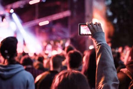 Close-up van het opnemen van video met smartphone tijdens een concert. Getinte foto Stockfoto