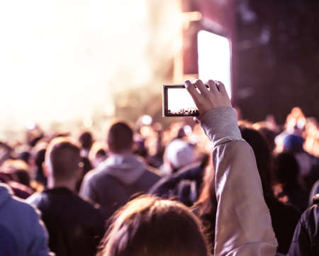 Close up of recording video with smartphone during a concert. Toned picture Imagens