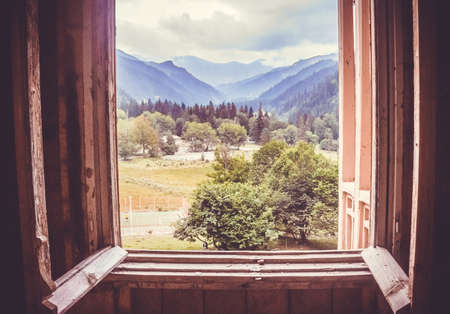 Campo de verano y las montañas visto a través de la ventana en la región de Racha, Georgia, el Cáucaso. Imagen virada Foto de archivo - 31727227