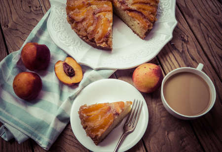 teatime: Delicious homemade nectarine cake on wooden background. Toned picture