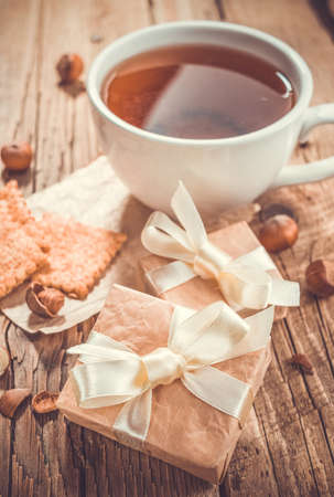 Cup of tea with gift boxes on old wooden background photo