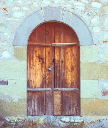 Old door with lock and stone wall. Toned picture photo