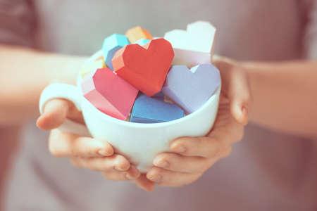Bright papier harten in mok in handen van de vrouw. getinte foto Stockfoto