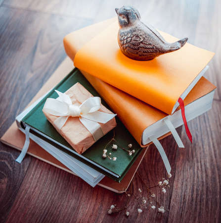 Pile of books with gift box on wooden background. Toned picture photo