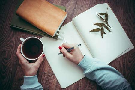 As mãos da mulher desenhando ou escrevendo no caderno aberto na mesa de madeira. Imagem tonificada