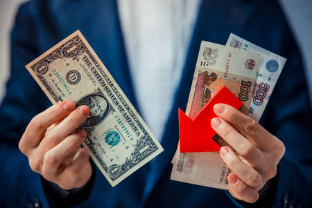 roubles: Business person holds roubles, dollars and red arrow. Devaluation of the Russian rouble.