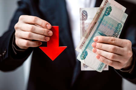 roubles: Business person holds roubles and red arrow. Devaluation of the Russian rouble. Stock Photo