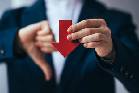 Business person holds red arrow and shows thumb down