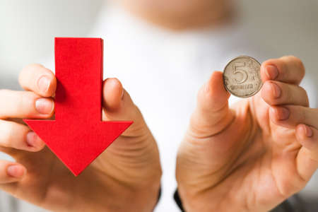 roubles: Businessman holds roubles and red arrow. Devaluation of the Russian rouble. Stock Photo