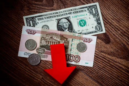 devaluation: Coins and banknotes of russian roubles on us dollar bill. Devaluation of the Russian rouble.