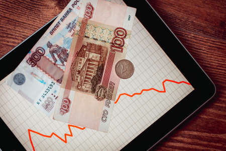 devaluation: Coins and banknotes of russian roubles on tablet with fluctating graph. Devaluation of the Russian rouble.  Toned picture