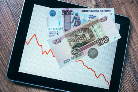 roubles: Coins and banknotes of russian roubles on tablet with fluctating graph. Devaluation of the Russian rouble. Stock Photo