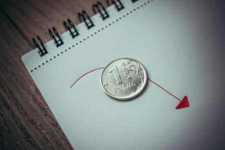 devaluation: Coin of russian rouble on notepad. Devaluation of the Russian rouble.  Toned picture