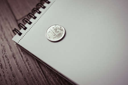 Coin of russian rouble on notepad. Devaluation of the Russian rouble. Toned picture photo