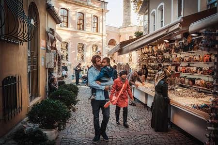 Istanbul, Turkije - 23 oktober 2014: Vader loopt met zijn kinderen langs de straat markt in Ortakoy aquare in Istanbul, Turkije. Gestemd beeld.